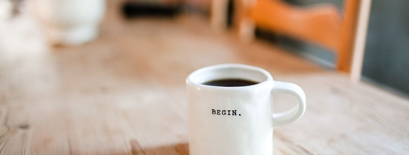 "Cup of coffee printed with the word ""begin"" to mark the start of a positive morning"